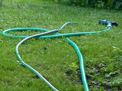A green color PVC garden hose is placed on the grassland.