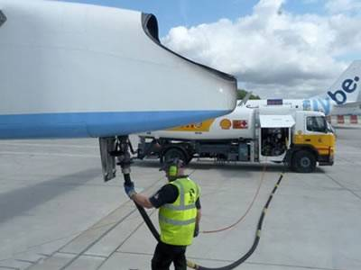 A oil tank is refueling a plain in the airport and a worker is holding the oil rubber hose.