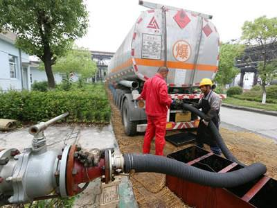 Two workers are transferring the oil into oil tank truck with oil rubber hose.
