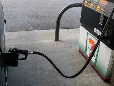 A machine is refueling automobile with oil rubber hose in the oil station.