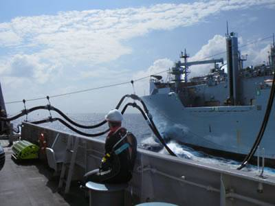 Two oil rubber hose lines are placed between two boats on the sea.