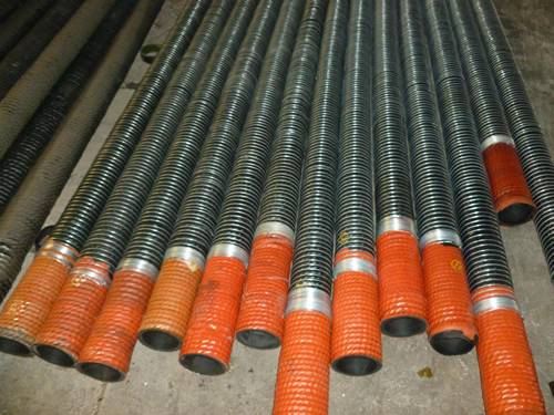 Several oil rubber hose with spiral wire sleeves on the ground.