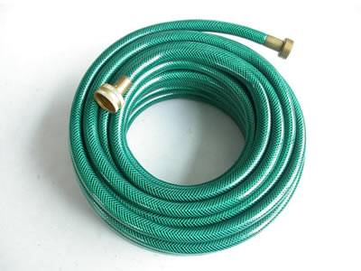 A roll of green color transparent PVC garden hose on the white background.