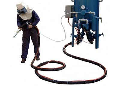 A worker holding the sandblasting hose connected with machine is shotting sand.